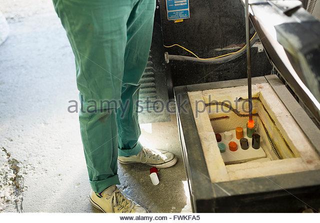 Glassblower melting clay in workshop - Stock Image