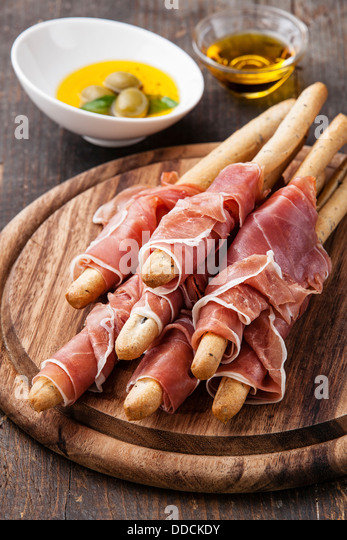 Bread sticks with ham on wooden background - Stock Image