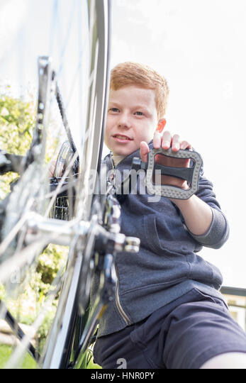 A boy maintaining his bike - Stock Image