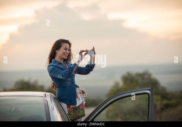 Young woman taking picture with her phone, Mineral de Pozos, Guanajuato, Mexico, North America - Stock Image