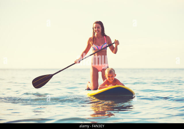 Mother and son stand up paddling at sunrise, Summer fun outdoor lifestyle - Stock Image