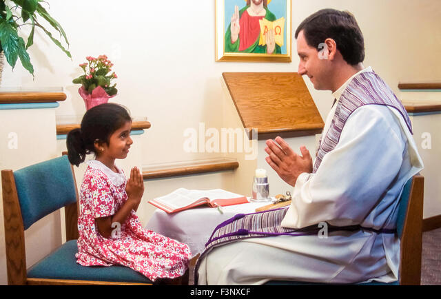 Young girl with priest during Reconcilliation MR ©Myrleen Pearson - Stock-Bilder