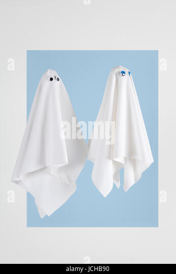 Couple of white sheet ghost with doll's eyes isolated on a white background whith blue frame. Minimal pop still - Stock Image