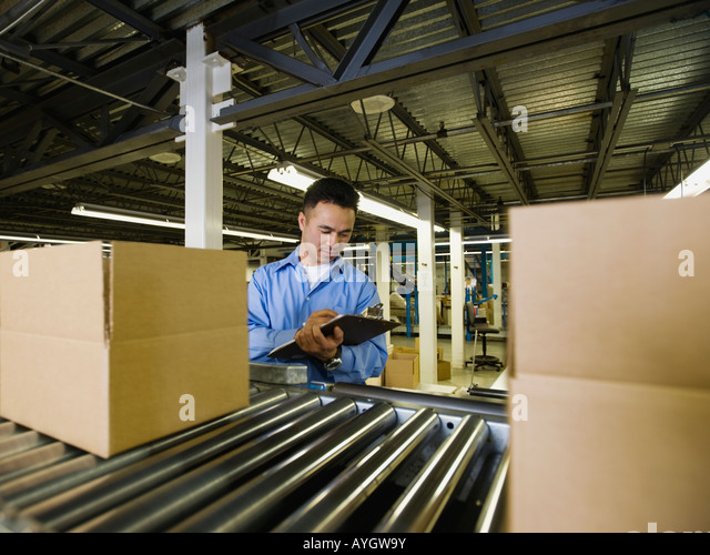 Asian male factory worker checking product - Stock Image