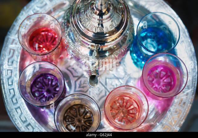 Colourful Moroccan tea glasses with tea pot in a tea tray. - Stock Image