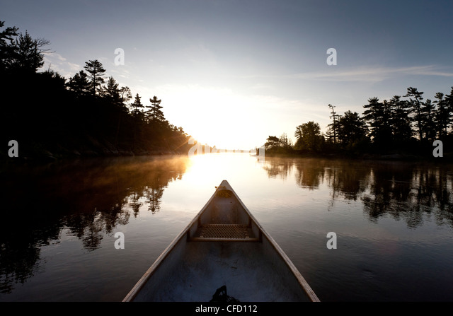 Bow of a canoe on the French River at dawn in French River Provincial Park, Ontario, Canada - Stock Image