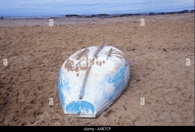 Small scratched blue and white rowing boat or dinghy inverted on much-used sandy beach with grey water beyond - Stock Image