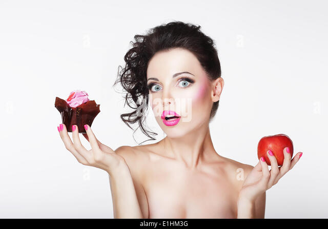 Dieting. Unsure Bewildered Girl Choosing Apple or Cake - Stock Image