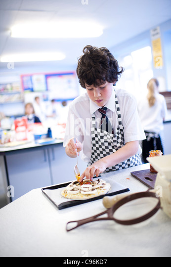 Secondary school children - a teenage boy in the foreground - in a food technology cookery cooking class, Wales - Stock Image