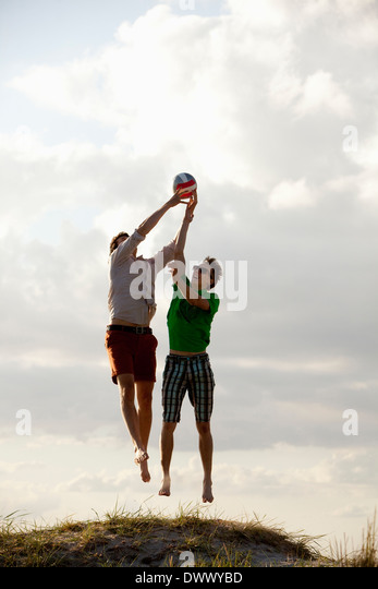Male friends in mid air trying to catch ball against sky - Stock Image