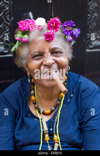 An elderly woman with flowers in her hair smoking a cigar in Havana,Cuba - Stock Image