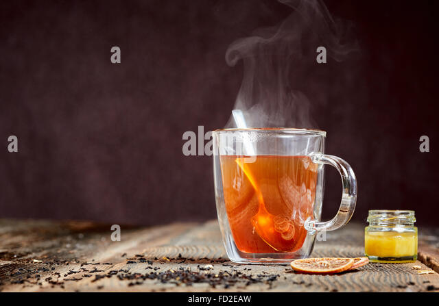 Steaming hot tea with honey and two orange slices on a wooden table - Stock Image