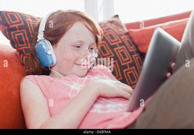 Girl in headphones using tablet computer - Stock-Bilder