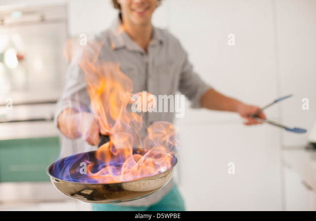 Man cooking with fire in kitchen - Stock Image