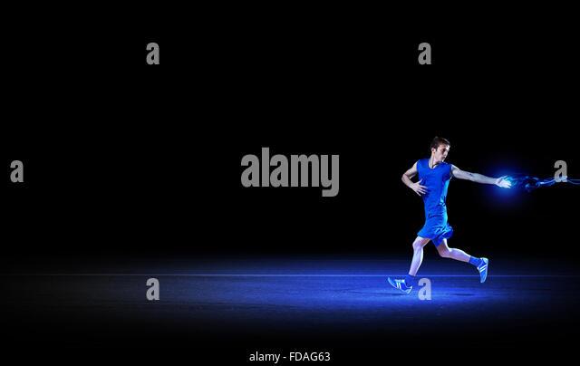 Running man in blue sport wear on black background - Stock-Bilder