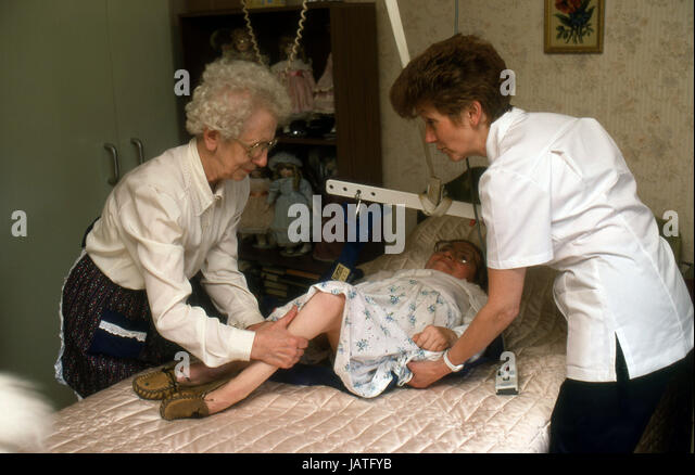 community nurse with patient at home with ageing mother assisting with hoisting daughter on the bed to a sitting - Stock Image