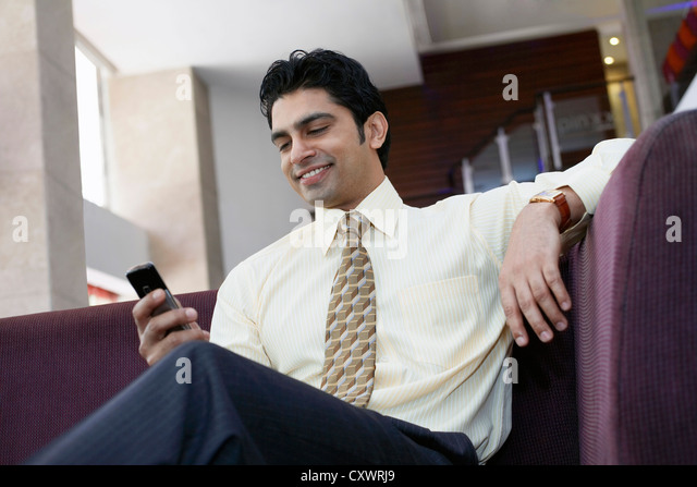 Businessman using cell phone on sofa - Stock Image