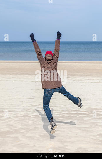 Woman jumping on beach, winter active lifestyle concept. - Stock-Bilder