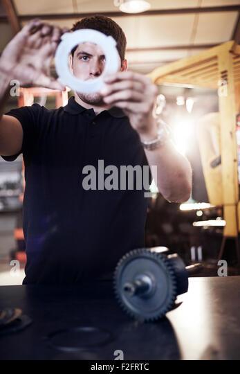 Mechanic examining part in auto repair shop - Stock Image