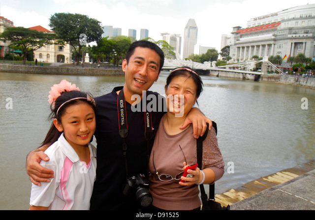Singapore Singapore River Boat Quay Asian man woman couple father mother girl daughter family Chinese hugging - Stock Image