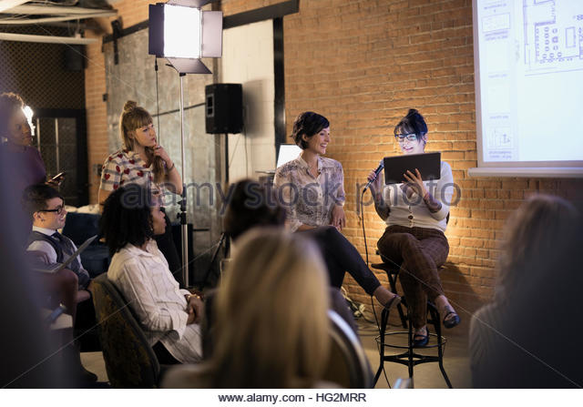 Female designers with microphone and digital tablet leading conference meeting - Stock Image