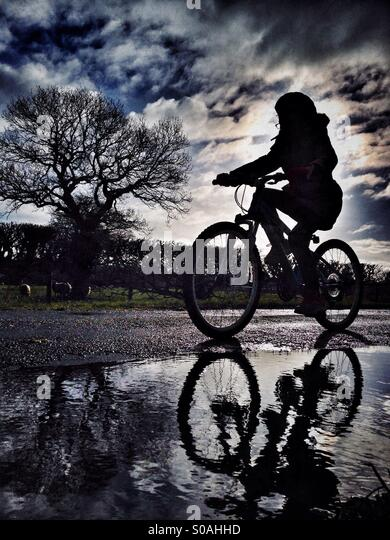 Young girl on bike in silhouette reflected in puddle - Stock Image