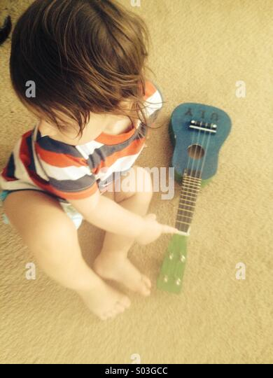 Toddler with ukulele - Stock Image