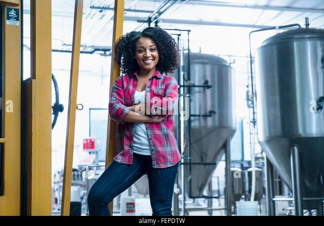 Mid adult woman in brewery leaning against yellow fork lift truck, arms folded looking at camera smiling - Stock Image