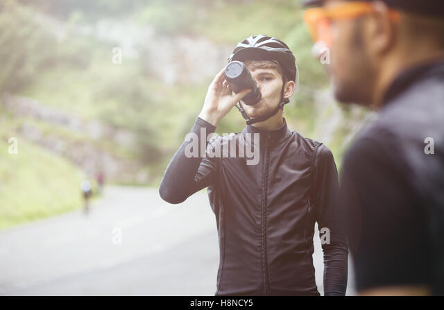 A young cyclist having a drink from his bottle in Cheddar George, U.K - Stock Image