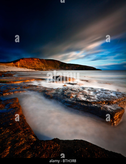 A stormy Dunraven Bay in warm evening light - Stock Image