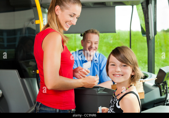 Mother and child boarding a bus and buying a ticket - Stock Image
