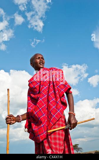 Kenya Masai Mara Masai warrior in red traditional wrap and stick in Masai Mara National Park in reserve #9 - Stock-Bilder