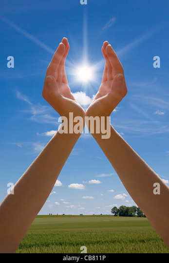 Hands Holding sun - Stock Image