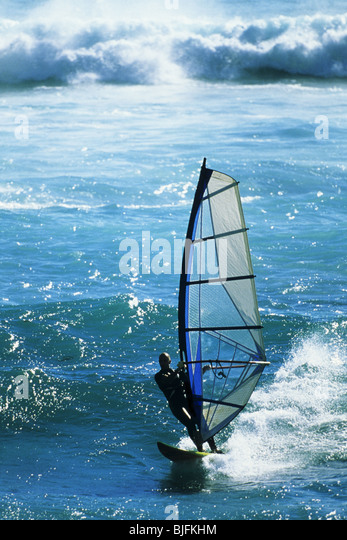 Windsurfer in action on the ocean against crashing waves - Stock Image