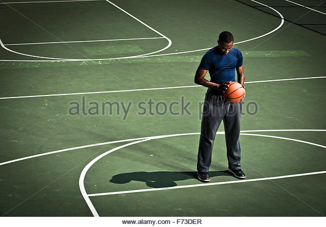 A basketball player practices free throws. - Stock Image