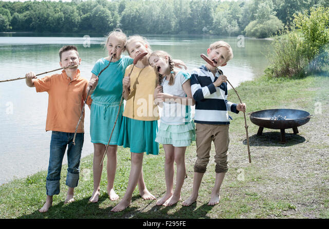 Group of friends eating sausages with breads at lakeside, Bavaria, Germany - Stock Image