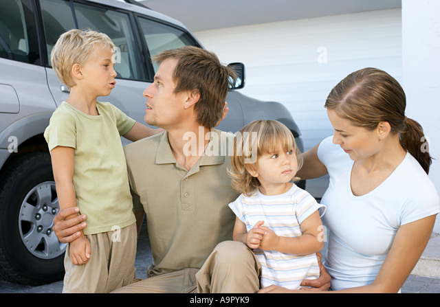 Mother and father comforting their children - Stock Image