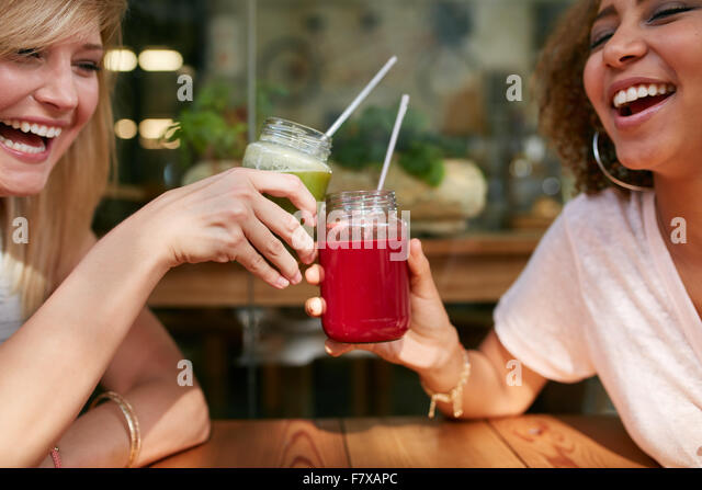 Close up shot of young friends toasting drinks at sidewalk cafe. Two happy women enjoying drinks and chat at outdoor - Stock Image