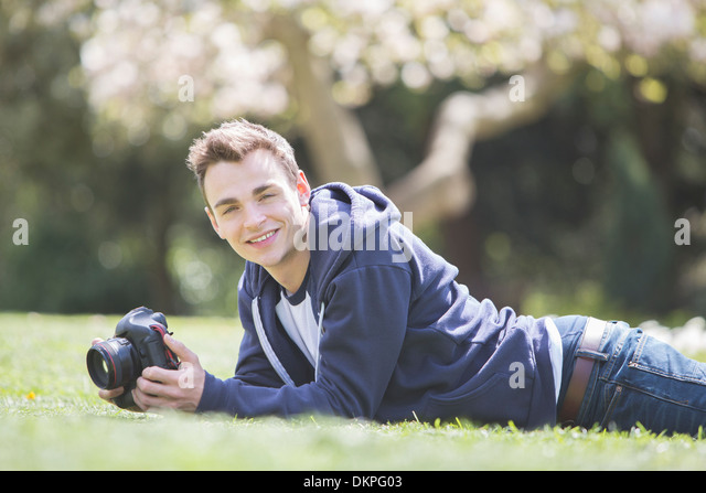 Man laying with camera in park - Stock Image