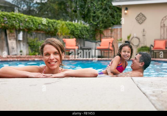Head and shoulders of mid adult woman with family in pool looking at camera smiling - Stock Image