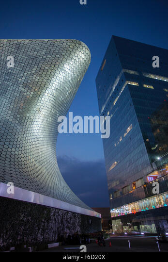 The curves of the Soumaya Museum of Art contrast with a modern high rise building in Mexico City, Mexico. - Stock Image