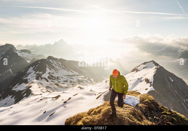 Young male mountain trekker on top of ridge in Bavarian Alps, Oberstdorf, Bavaria, Germany - Stock Image