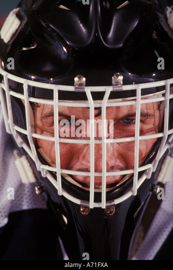 Close up view of a sweaty hockey goalie s face through his mask - Stock Image