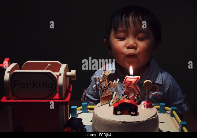 Cute Boy With Eye Closed Blowing Birthday Candle On Cake In Darkroom - Stock Image