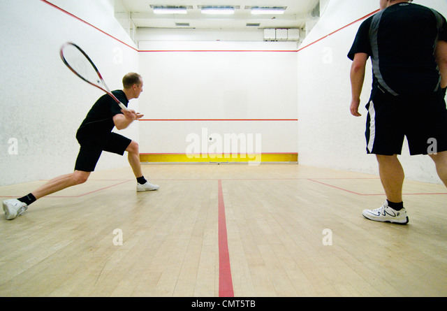 Rear view of two men playing squash - Stock Image