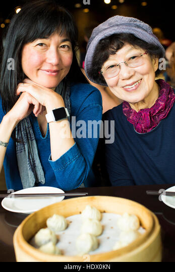 Older Japanese mother and daughter smiling in restaurant - Stock Image