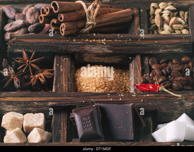 Old wooden box with set of coffee and cocoa beans, sugar cubes, dark chocolate, cinnamon and anise. See series - Stock Image