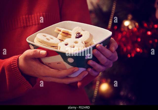 Girl holding bowl with Christmas cookies - Stock Image