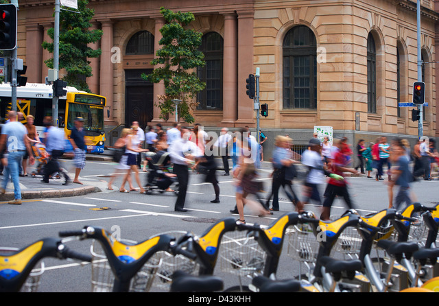 Brisbane City Council Bus in the city and pedestrians - Stock Image