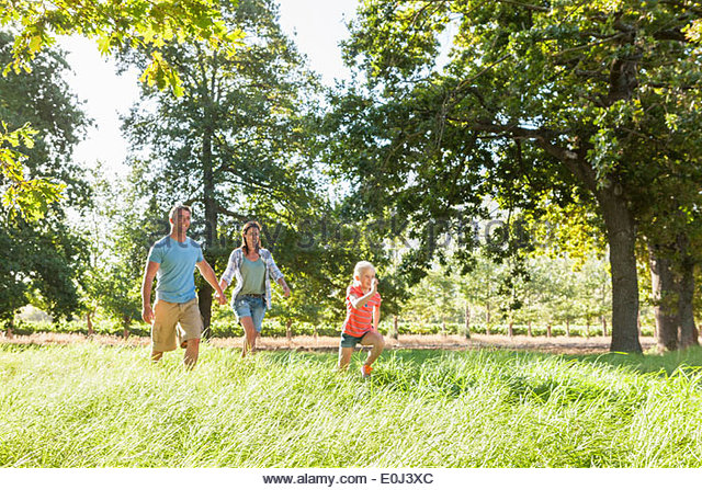 Family Enjoying Walk In Beautiful Countryside - Stock Image